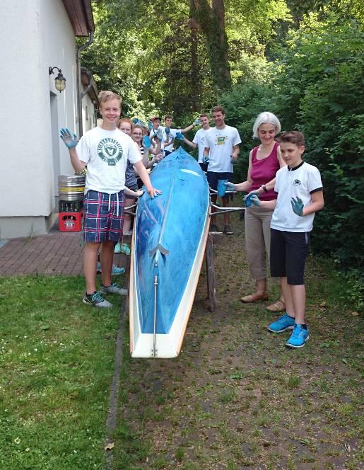 Die Jugendlichen streichen ein Boot