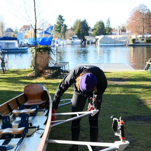 Eine Rudererin putzt das Boot nach dem Rudern