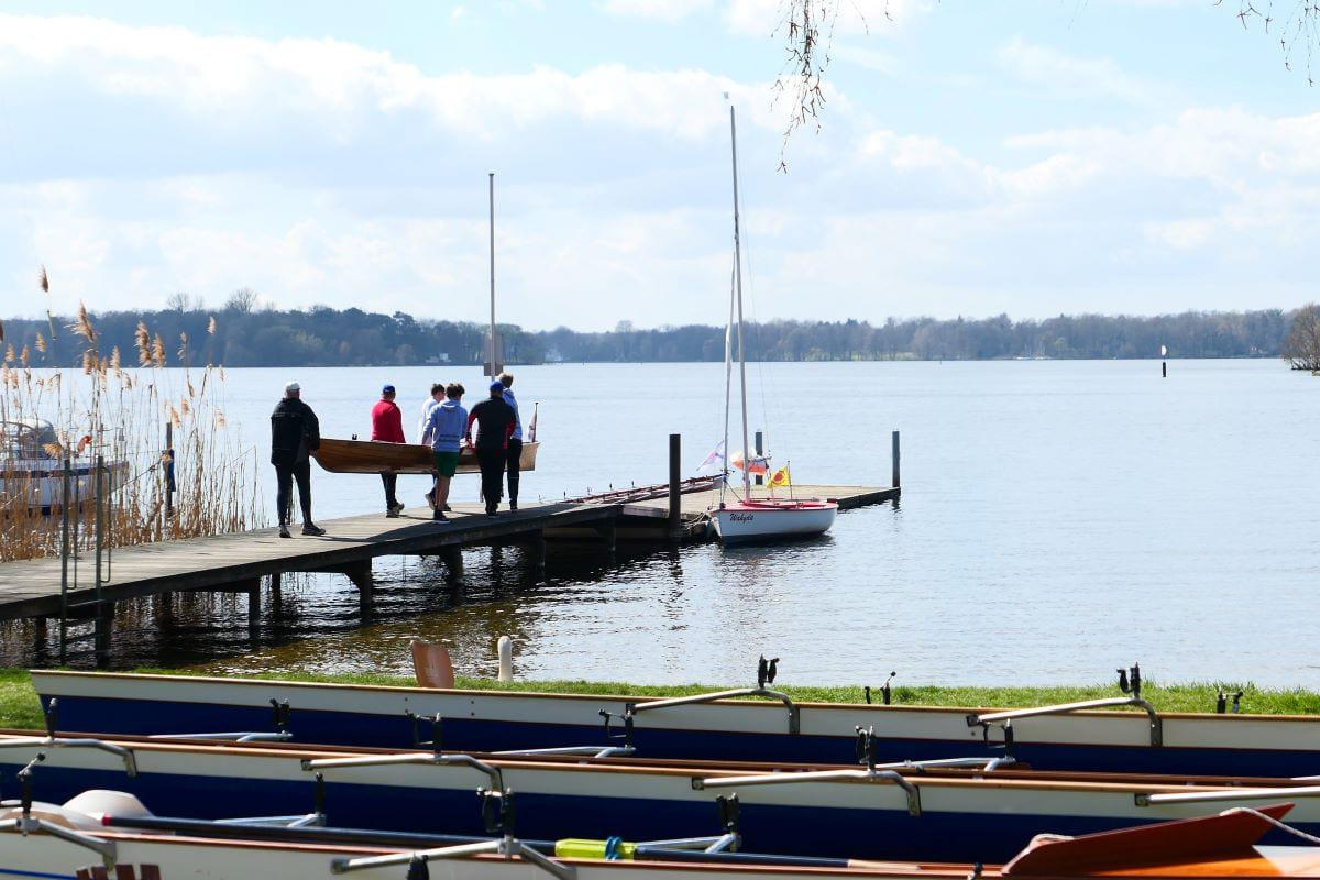 Ein Ruderboot wird ins Wasser getragen