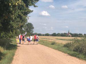 Eine Gruppe Ruderer läuft ins nächste Dorf