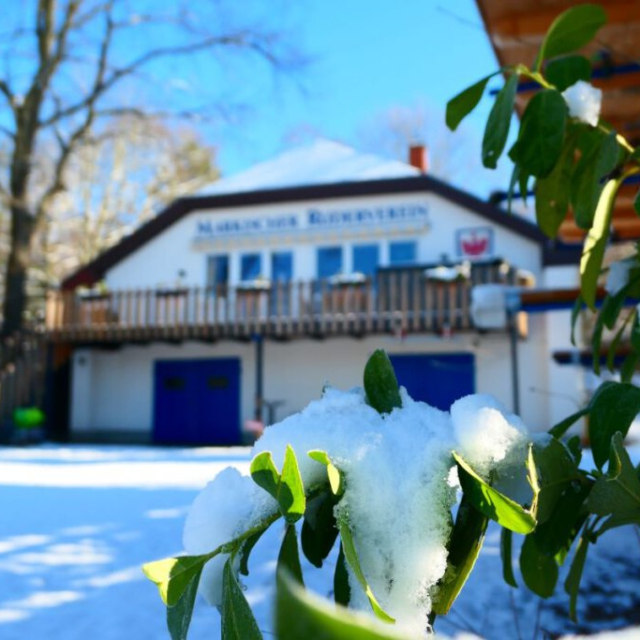 Verschneite Pflanzen und das winterliche Bootshaus